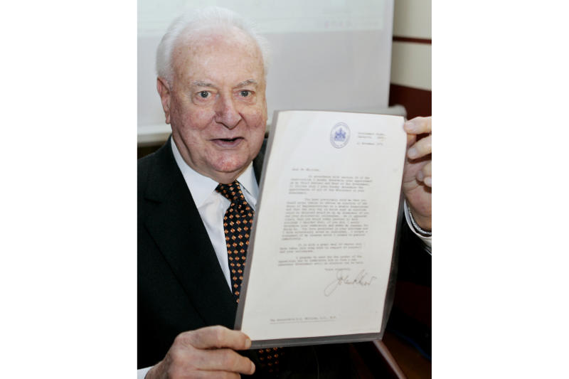 FILE - In this Nov. 7, 2005, file photo, former Australian Prime Minister Gough Whitlam holds up the original copy of his dismissal letter he received from then Governor-General Sir John Kerr on Nov. 11, 1975, at a book launch in Sydney, Australia. The High Court's majority decision in historian Jenny Hocking's appeal on Friday, May 29, 2020 overturned lower court rulings that more than 200 letters between the monarch of Britain and Australia and Governor-General Sir John Kerr before he dismissed Prime Minister Gough Whitlam's government were personal and might never be made public. (AP Photo/Mark Baker, File)