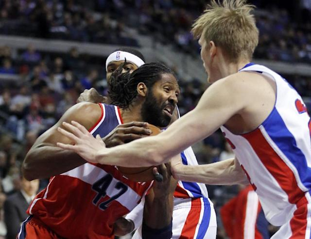 Washington Wizards forward Nene (42) drives against Detroit Pistons guard Kyle Singler, right, during the first half of an NBA basketball game, Monday, Dec. 30, 2013, in Auburn Hills, Mich. (AP Photo/Duane Burleson)