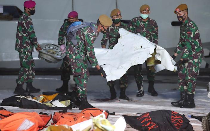 Indonesian soldiers carry pieces of the Sriwijaya Air passenger jet wreckage recovered at the search and rescue command center in Jakarta - AP