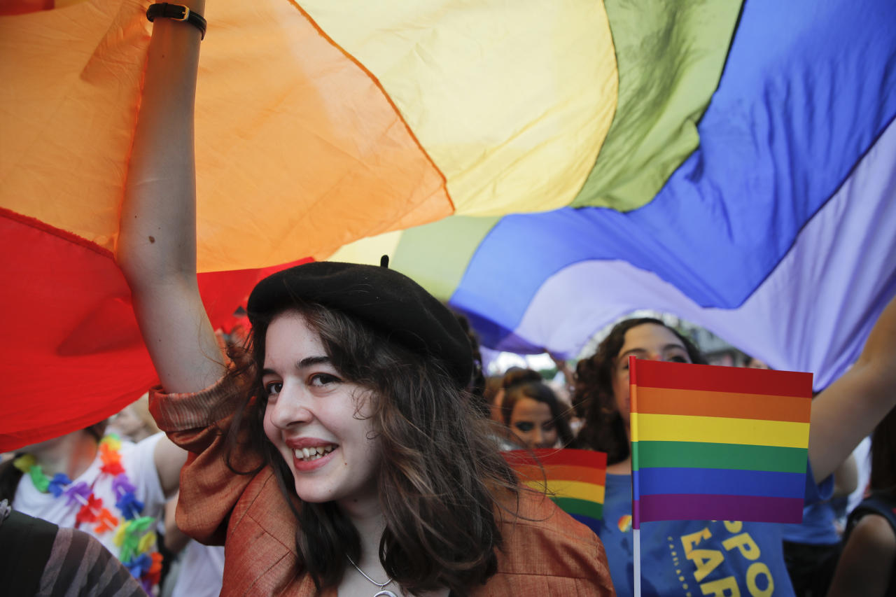 <p>A girl smiles under a large rainbow flag during the gay pride parade in Bucharest, Romania, Saturday, June 9, 2018. People taking part in the gay pride parade in the Romanian capital demanded more rights and acceptance for same-sex couples. (Photo: Vadim Ghirda/AP) </p>