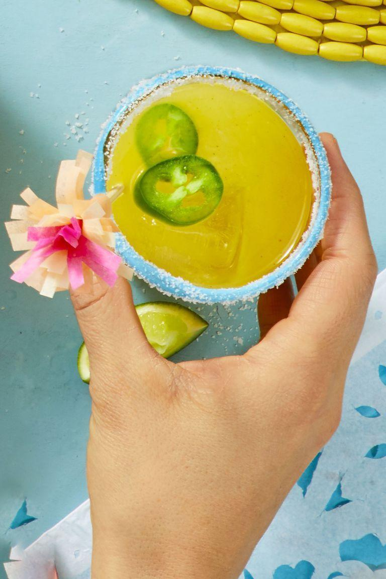 """<p>Kick your party up a notch with this spicy cocktail on the rocks. </p><p><em><a href=""""https://www.goodhousekeeping.com/food-recipes/party-ideas/a19865233/jalapeno-mango-margarita-recipe/"""" rel=""""nofollow noopener"""" target=""""_blank"""" data-ylk=""""slk:Get the recipe for Jalapeño Mango Margarita »"""" class=""""link rapid-noclick-resp"""">Get the recipe for Jalapeño Mango Margarita »</a></em></p>"""