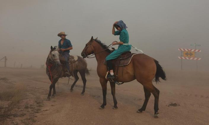 Horse riders surrounded by smoke from the Richard Spring fire as it moves toward Ashland, Montana.