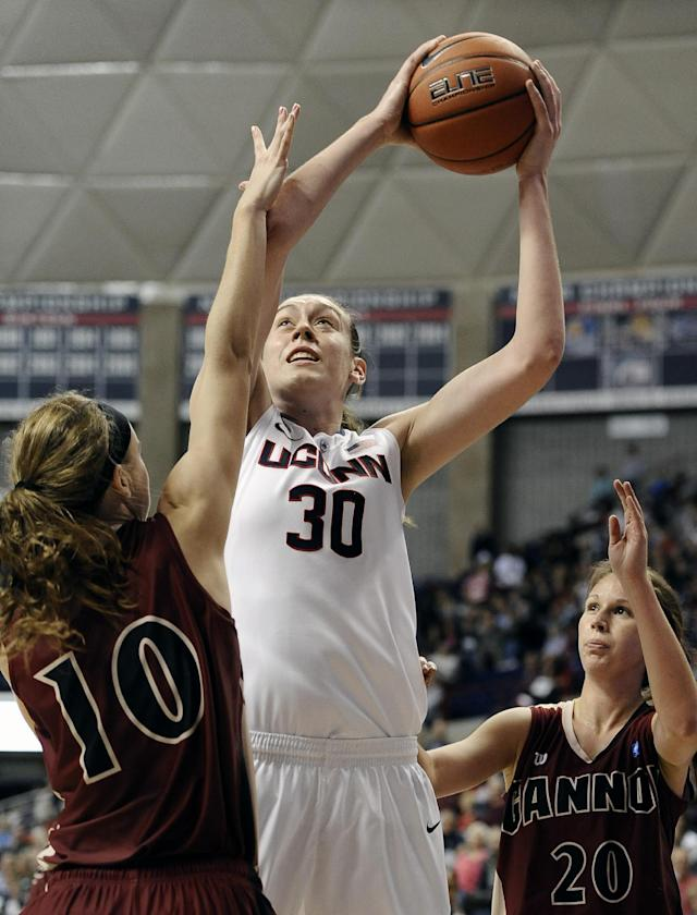 Connecticut's Breanna Stewart, center, goes up for a basket as Gannon's Brianna Brennan, left, and Brittany Batts, right, defend during the first half of an exhibition NCAA college basketball game, Friday, Nov. 1, 2013, in Storrs, Conn. (AP Photo/Jessica Hill)