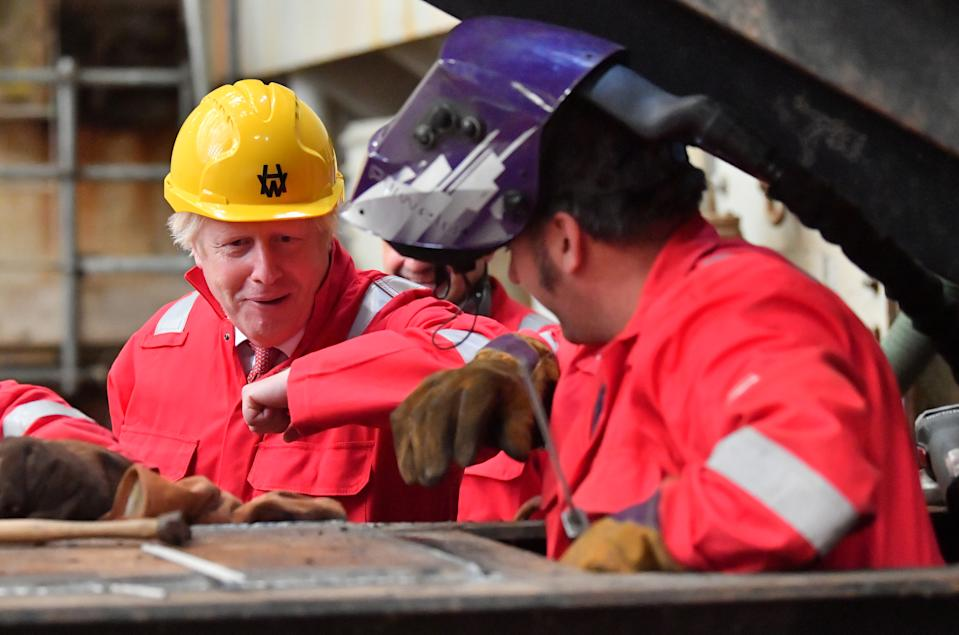 Prime Minister Boris Johnson elbow bumps a welder during his visit to Appledore Shipyard in Devon which was bought by InfraStrata, the firm which also owns Belfast's Harland & Wolff (H&W), in a �7 million deal.