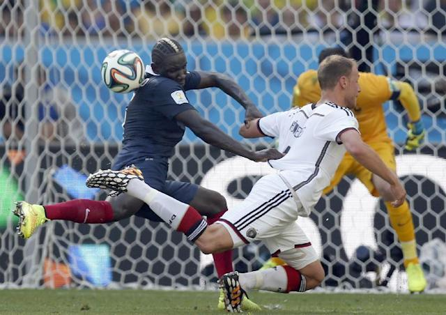 France's Mamadou Sakho heads the ball as he grabs Germany's Mats Hummels by the jersey during the World Cup quarterfinal soccer match between Germany and France at the Maracana Stadium in Rio de Janeiro, Brazil, Friday, July 4, 2014. (AP Photo/Frank Augstein)