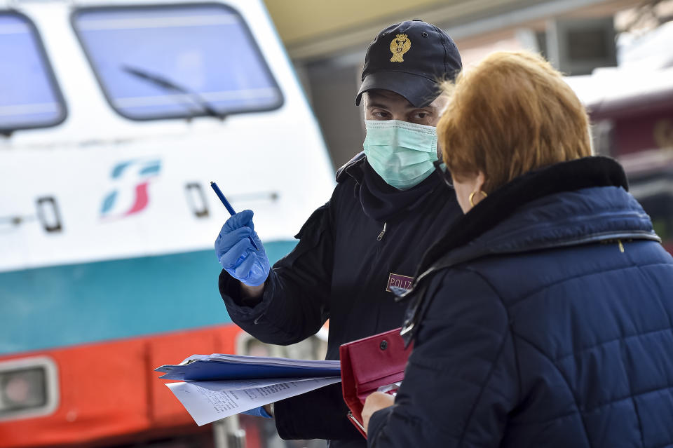 TORINO PORTA NUOVA RAILWAY STATION, TURIN, ITALY - 2020/03/09: Police officer checks a passenger leaving from Turin Porta Nuova train station. The Italian government imposed a virtual lockdown on the north of the country as part of measures to stop the spread of the coronavirus COVID-19 outbreak in Italy. (Photo by Nicolò Campo/LightRocket via Getty Images)