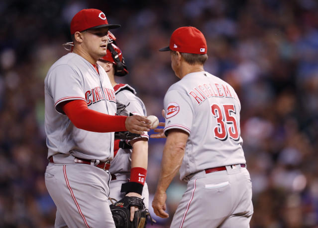 Cincinnati Reds starting pitcher Sal Romano, left, hands the ball to interim manager Jim Riggleman who pulls him fter he gave up an RBI-triple to Colorado Rockies pinch-hitter Noel Cuevas in the sixth inning of a baseball game Friday, May 25, 2018, in Denver. (AP Photo/David Zalubowski)