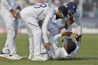 Indian cricket captain Virat Kohli, center, congratulates Rohit Sharma, on ground, for taking a catch to dismiss Bangladesh's Mominul Haque during the first day of the second test match between India and Bangladesh in Kolkata, India, Friday, Nov. 22, 2019. (AP Photo/Bikas Das)