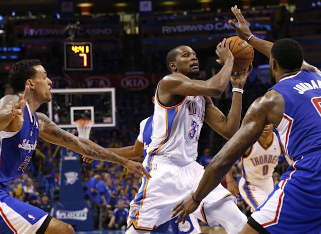 Oklahoma City Thunder forward Kevin Durant (35) drives between Los Angeles Clippers forward Matt Barnes (22) and center DeAndre Jordan (6) in the third quarter of Game 1 of the Western Conference semifinal NBA basketball playoff series in Oklahoma City, Monday, May 5, 2014. Los Angeles won 122-105. (AP Photo/Sue Ogrocki)