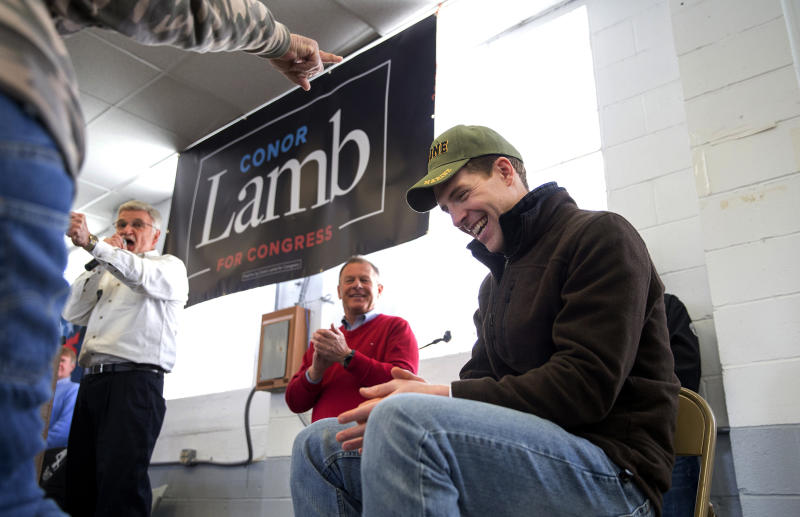 Retired coal miner David Fibazzo, left pointing, of Coal Center, places his hat on top of Democratic candidate Conor Lamb's head during a rally with the United Mine Workers of America, Sunday, March 11, 2018, at the Greene County Fairgrounds in Waynesburg, Pa. Lamb is asking Pennsylvania's coal country for help in the first congressional election of 2018, viewed as a key test of support for Republicans ahead of November's midterms. (Antonella Crescimbeni/Pittsburgh Post-Gazette via AP)