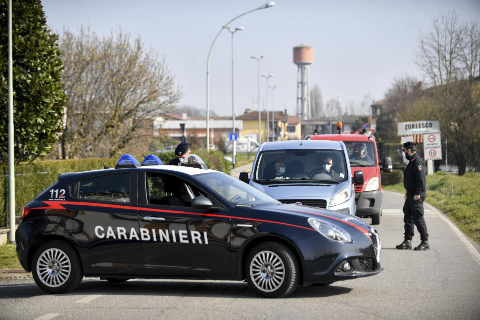 Carabinieri (Italian paramilitary police) officers set a road block in Zorlesco, Northern Italy, Monday, Feb. 24, 2020. Italy scrambled to check the spread of Europe's first major outbreak of the new viral disease amid rapidly rising numbers of infections. Road blocks were set up in at least some of 10 towns in Lombardy at the epicenter of the outbreak, to keep people from leaving or arriving. (Claudio Furlan/Lapresse via AP)