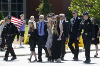 Family members escorted by law enforcement officers lead a processional to the Holmes Convocational Center for the funeral services of Watauga County Sheriff's Deputies Sgt. Chris Ward and K-9 Deputy Logan Fox in Boone, N.C., Thursday, May 6, 2021. The two deputies were killed in the line of duty. (AP Photo/Gerry Broome)