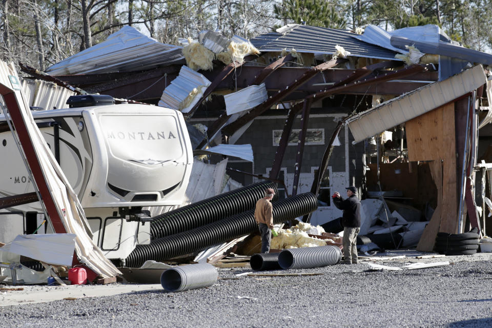 Owner Richard Dobkin, right, photographs the damage at Ocean Ridge Storage Solutions in Brunswick County, North Carolina.