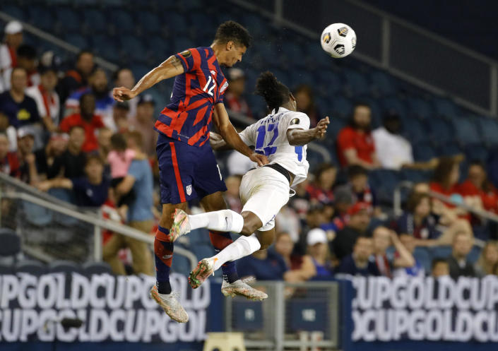 U.S. defender Miles Robinson, left, and Martinique forward Johnny Marajo go up for the ball during the first half of a CONCACAF Gold Cup soccer match in Kansas City, Kan., Thursday, July 15, 2021. (AP Photo/Colin E. Braley)