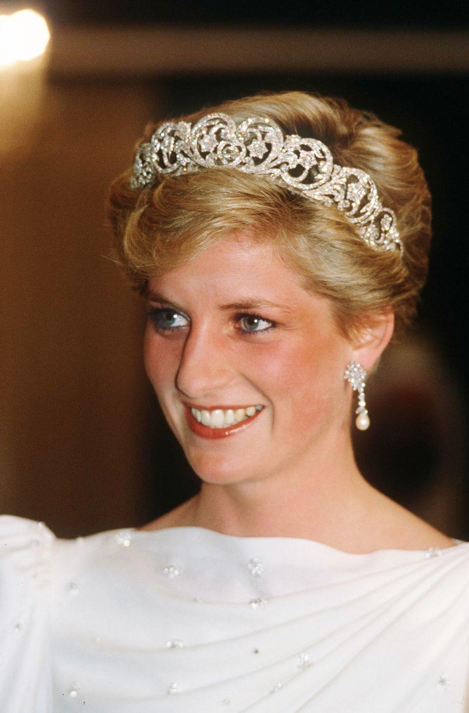 <p>During a 1986 visit to Bahrain, Diana glowed in the Spencer tiara, diamond and pearl drop earrings, and a boatneck white and silver gown. </p>