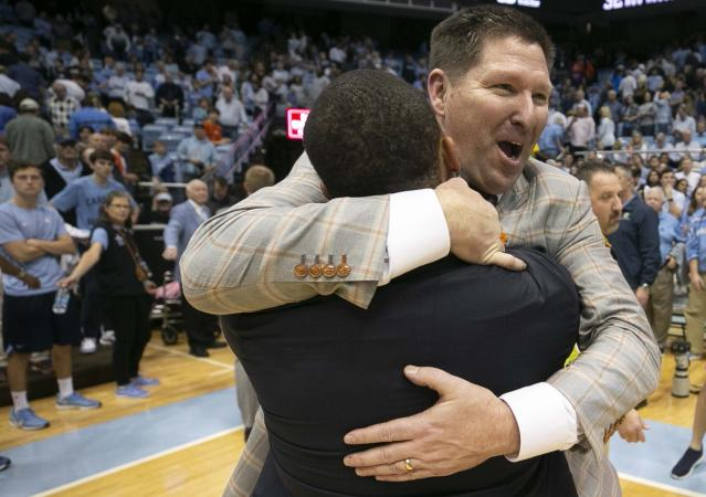 Clemson coach Brad Brownell embraces assistant coach Anthony Goins as they celebrate the win over North Carolina after an NCAA college basketball, Saturday, Jan. 11, 2020, at the Smith Center in Chapel Hill, N.C. (Robert Willett/The News & Observer via AP)