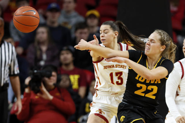 Iowa guard Kathleen Doyle (22) passes around Iowa State guard Adriana Camber (13) during the first half of an NCAA college basketball game, Wednesday, Dec. 11, 2019, in Ames, Iowa. (AP Photo/Charlie Neibergall)