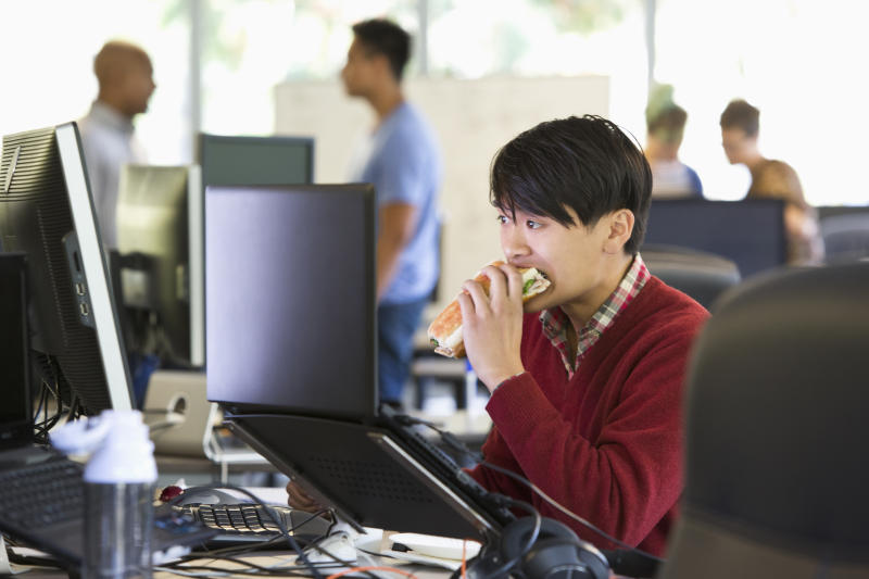 Businessman eating at office desk