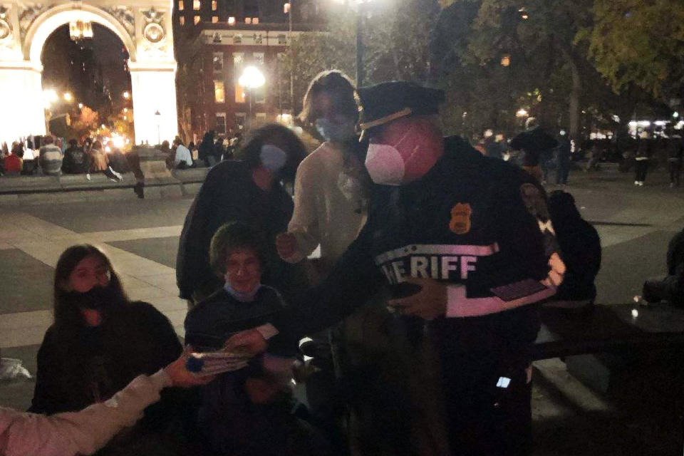 This photo provided by the New York City Sheriff, shows a Deputy Sheriff distributing medical face masks in New York's Washington Square Park, Oct. 21, 2020. A crackdown on COVID-19 restriction violators has drawn attention to a sheriff in New York City few knew existed. Sheriff Joseph Fucito has worn the badge for the past six years in a civil-enforcement post that hasn't carried the notoriety of his counterparts with roots in Wild West folklore. (New York City Sheriff via AP)