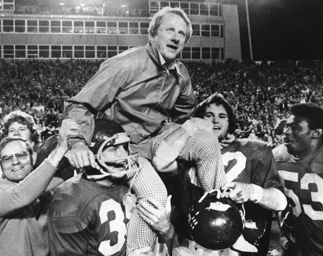 FILE - In this Dec. 6, 1975, file photo, Arkansas coach Frank Broyles is carried from the field by players Teddy Barnes, left, and Richard LaFargue (52) following his team's 30-6 NCAA college football game victory over Texas A & M in Little Rock, Ark. Broyles, now 89, is Arkansas' most successful football coach and unquestioned patriarch of athletics still comes into the office every day. (AP Photo/Ferd Kaufman, File)