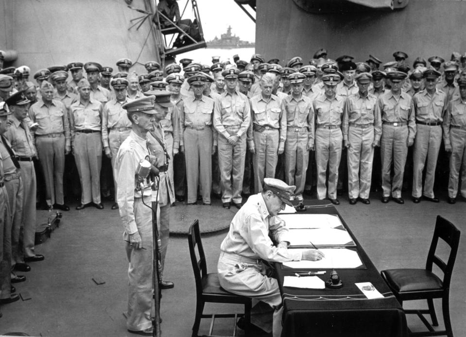 FILE - Gen. Douglas MacArthur signs the Japanese surrender documents on Sept. 2, 1945, aboard the USS Missouri in Tokyo Bay. Standing behind him are Lt. Gen. Jonathan Wainwright, left foreground, who surrendered Bataan to the Japanese, and British Lt. Gen. A. E. Percival, next to Wainwright, who surrendered Singapore, as they witness with other American and British officers the ceremony marking the end of World War II. Several dozen aging U.S. veterans, including some who were in Tokyo Bay on the day that ended World War II, will gather on the battleship in Pearl Harbor in September to mark the 75th anniversary of Japan's surrender. (U.S. Navy, File)