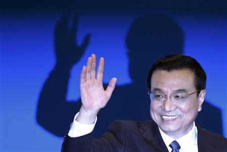 China's Premier Li Keqiang waves during a news conference, after the closing ceremony of the Chinese National People's Congress (NPC) at the Great Hall of the People, in Beijing March 13, 2014. REUTERS/Barry Huang