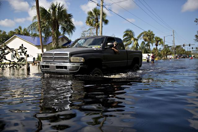 <p>A resident looks out the window of his truck as he navigates a flooded street in Bonita Springs, Fla., on Sept. 12, 2017. (Photo: Daniel Acker/Bloomberg via Getty Images) </p>