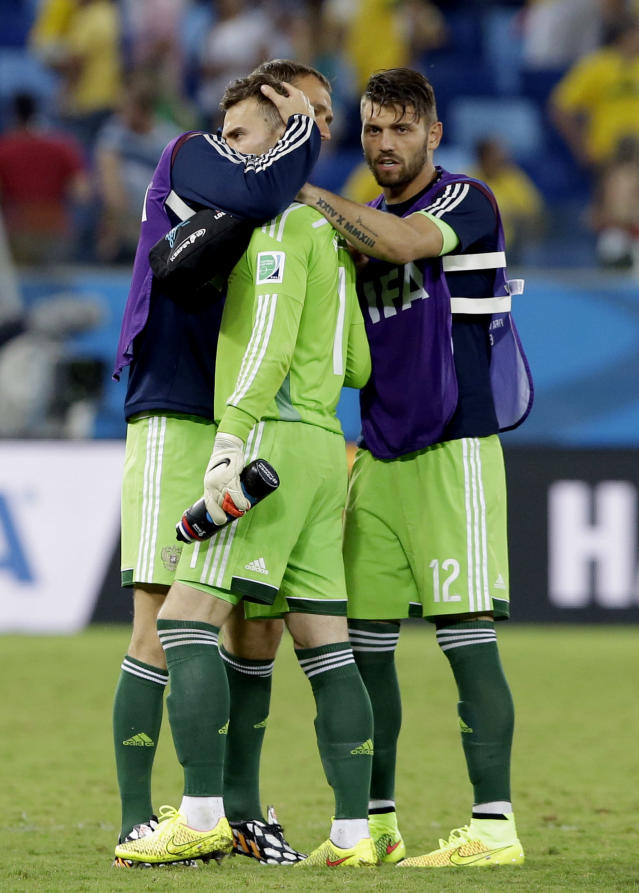 Russian players console Russia's goalkeeper Igor Akinfeev, center, after the group H World Cup soccer match between Russia and South Korea at the Arena Pantanal in Cuiaba, Brazil, Tuesday, June 17, 2014. The match ended in a 1-1 draw. (AP Photo/Lee Jin-man)