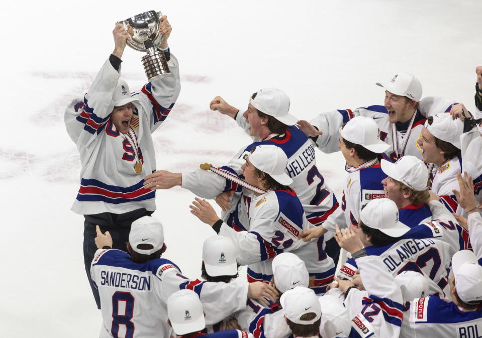 United States' Cam York (4) hoists the trophy after the team's win over Canada in the title game in the IIHF World Junior Hockey Championship, Tuesday, Jan. 5, 2021, in Edmonton, Alberta. (Jason Franson/The Canadian Press via AP)