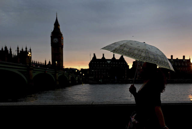 Jul 27, 2012; London, United Kingdom; A pedestrian walks down the road with Big Ben in the background carrying an umbrella as rain falls during the Opening Ceremonies to start the 2012 Olympic Games. Mandatory Credit: Andrew Weber-USA TODAY Sports