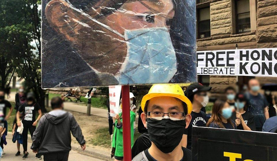 Ricker Choi is seen at a protest last year in Toronto with one of his paintings, depicting activist Agnes Chow. Photo: Handout/Ricker Choi