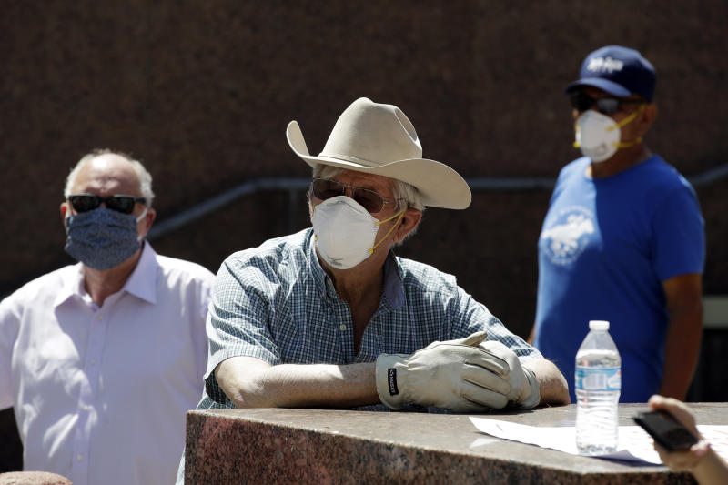 Horse racing supporters stand outside the Board of Supervisors building to protest the closing of Santa Anita Park as part to the state's stay-at-home measures amid the COVID-19 pandemic Tuesday, April 28, 2020, in Los Angeles. (AP Photo/Marcio Jose Sanchez)