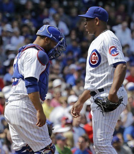 Chicago Cubs relief pitcher Carlos Marmol, right, reacts as he talks with catcher Welington Castillo during the eighth inning of a baseball game against the Cincinnati Reds in Chicago, Saturday, May 4, 2013. (AP Photo/Nam Y. Huh)