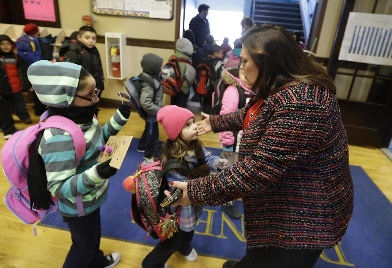 "In this Feb. 26, 2014 photo, Bennett Elementary School Principal Josette Buendia receives hugs from her students at the end of the school day in Detroit. Buendia couples fun - such as a weekly ""Popcorn Friday"" - with academic innovations, including one-on-one tutoring for her 4th and 5th graders via Skype with student volunteers at a suburban high school. (AP Photo/Carlos Osorio)"