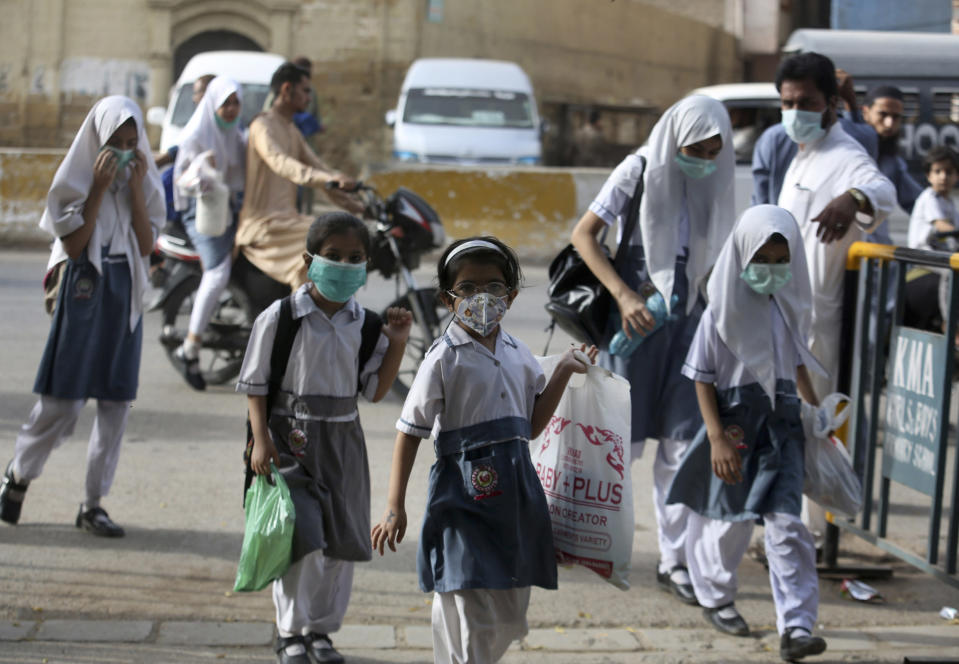 Student wearing face masks to help prevent the spread of the coronavirus arrive at a school in Karachi, Pakistan, Monday, June 21, 2021. Authorities of Pakistan's Sindh province reopened educational institutes following a steady decrease in deaths and infections from the coronavirus. (AP Photo/Fareed Khan)