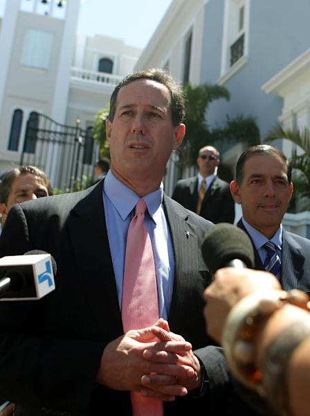 Republican presidential candidate, former Pennsylvania Sen. Rick Santorum, left, talks with reporters as he leaves La Fortaleza, or Fortess, where he met with the Commonwealth of Puerto Rico Governor Luis Fortuno, in San Juan, Puerto Rico, Wednesday March 14, 2012. (AP Photo/Dennis M. Rivera Pichardo)