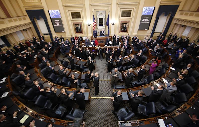 Virginia Gov. Bob McDonnell, center isle, waves to his wife as he arrives to deliver his State of the Commonwealth address before a joint session of the 2014 General Assembly at the Capitol in Richmond, Va., Wednesday, Jan. 8, 2014. McDonnell leaves office on Saturday. (AP Photo/Steve Helber)