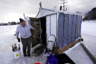 FILE - Steve Jesi of Middleton, Mass., steps out of a fishing shack to stretch his legs at Leighton's Smelt Camps, Wednesday, Feb. 10, 2021, in Bowdoinham, Maine. A late arriving winter has made it difficult for to collect data about the health of the smelt population. (AP Photo/Robert F. Bukaty)