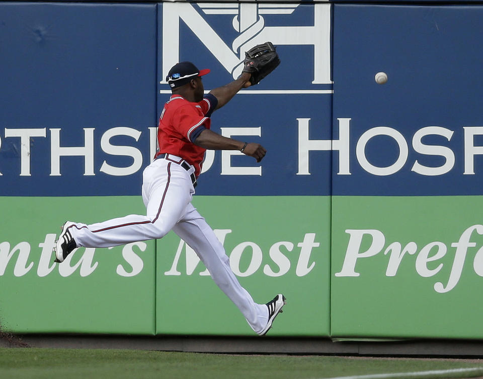 A ball hit for a triple by Washington Nationals' Denard Span gets past Atlanta Braves left fielder Justin Upton in the first inning of a baseball game in Atlanta, Friday, May 31, 2013. (AP Photo/John Bazemore)