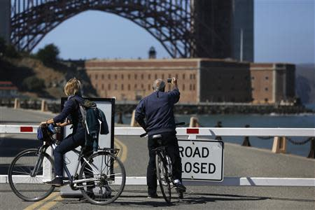 A bicyclist takes a photograph in front of the closed road gate to Fort Point National Historic Site, which has been closed due to the federal government shutdown, in San Francisco, California October 2, 2013. REUTERS/Stephen Lam