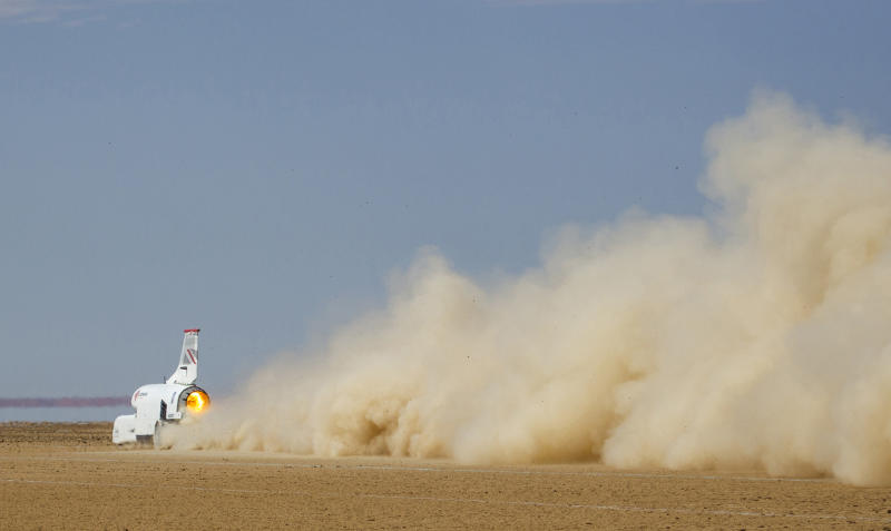 In this handout photo provided by Bloodhound, the vehicle speeds along the Hakskeenpan track in South Africa during trials to set a land speed record Friday, Nov. 8, 2019. Hitting 501 miles per hour on the South Africa's northern desert, the Bloodhound became one of the world's 10 fastest cars this week, on target for its goal to set a new land speed record. A jet that stays on earth, Bloodhound's next goal is to reach 550 miles per hour, possibly in the coming week. (Charlie Sperring/Bloodhound via AP)