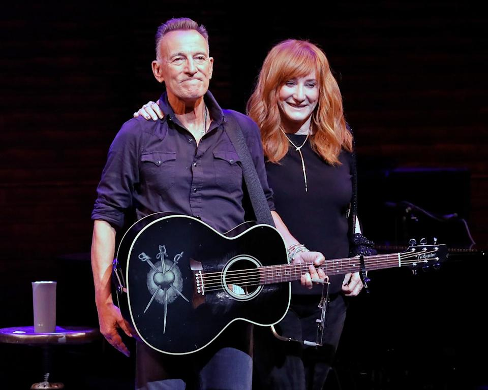 A man holding a guitar and a woman with her arm around him stand on a stage
