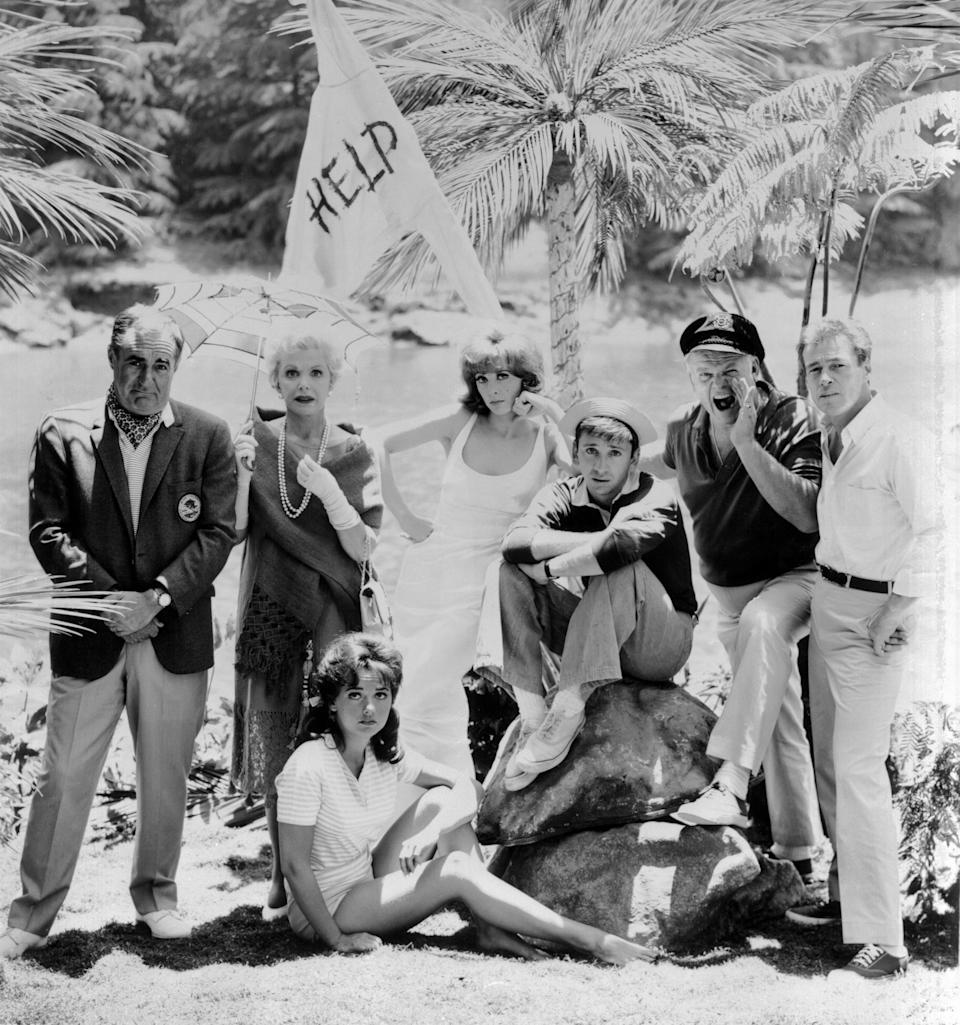"""Dawn Wells, seated, poses with fellow """"Gilligan's Island"""" cast members Jim Backus, standing left, Natalie Schafer, Tina Louise, Bob Denver, Alan Hale Jr. and Russell Johnson in a photo from the 1960s CBS sitcom."""