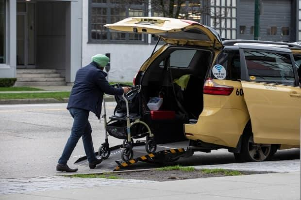 A taxi cab loads a walker into his wheelchair accessible van in Vancouver on Jan. 30, 2020.