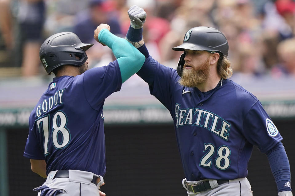 Seattle Mariners' Jake Fraley, right, and Jose Godoy celebrate after Fraley hit a two-run home run in the fourth inning of a baseball game against the Cleveland Indians, Sunday, June 13, 2021, in Cleveland. (AP Photo/Tony Dejak)