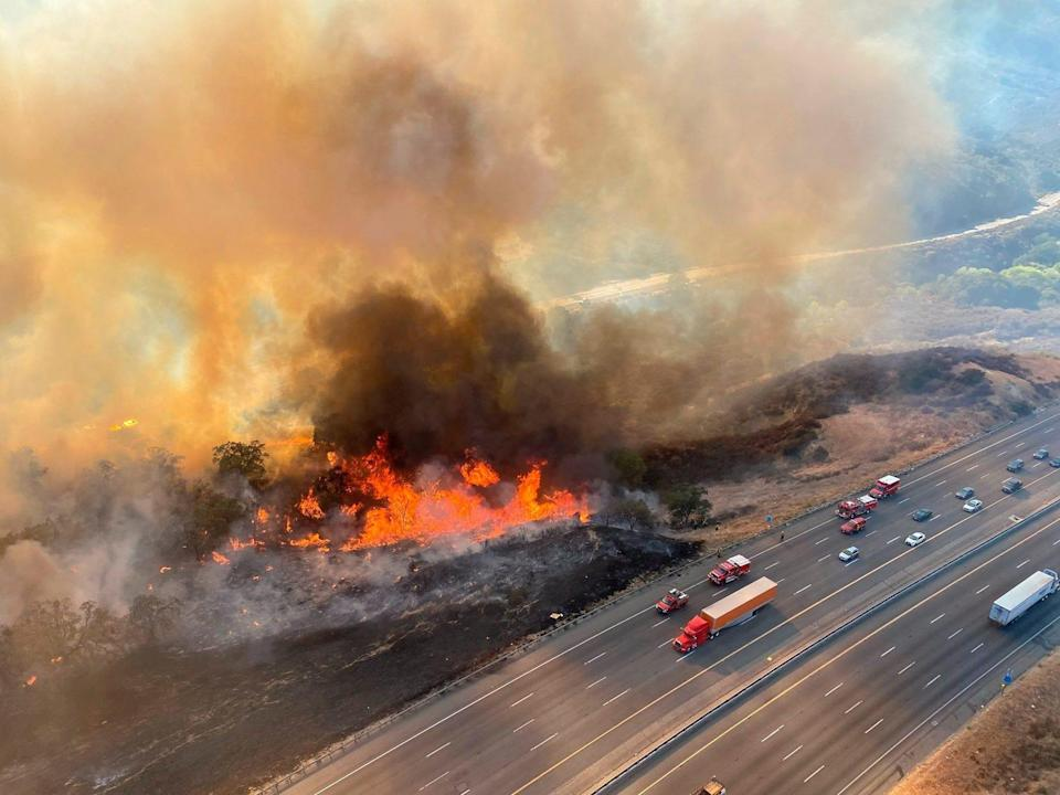 In this aerial photo released by the Los Angeles County Fire Department Air Operations traffic passes the Route fire, a brush wildfire off Interstate 5 north of Castaic, Calif., on Saturday, Sept. 11, 2021.