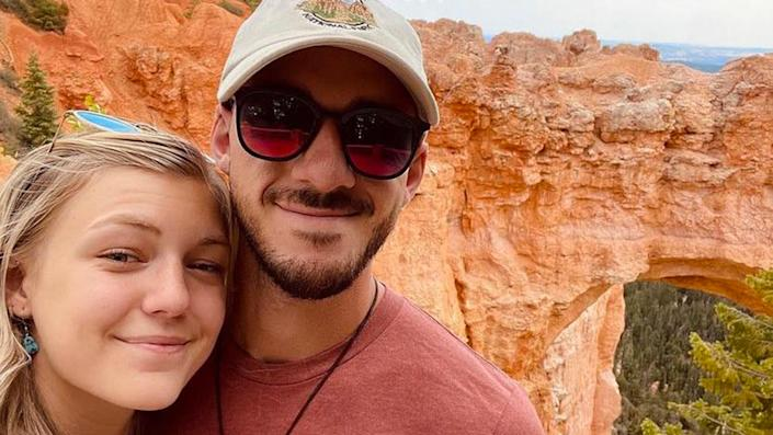 Gabby Petito and Brian Laundrie pose for a selfie in front of canyonland scenery.