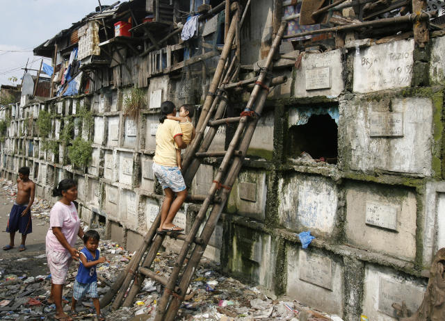 Residents climb into their houses atop gravestones inside a cemetery in Manila October 21, 2008. Many poor urban dwellers make their homes in public cemeteries, converting abandoned tombs and mausoleums into houses. The local government plan to move out the hundreds of people who live in the cemeteries around the city before the upcoming All Souls' Day, a day of remembrance for the dead when Catholics visit the graves of their relatives. REUTERS/Cheryl Ravelo (PHILIPPINES) - RTX9REV