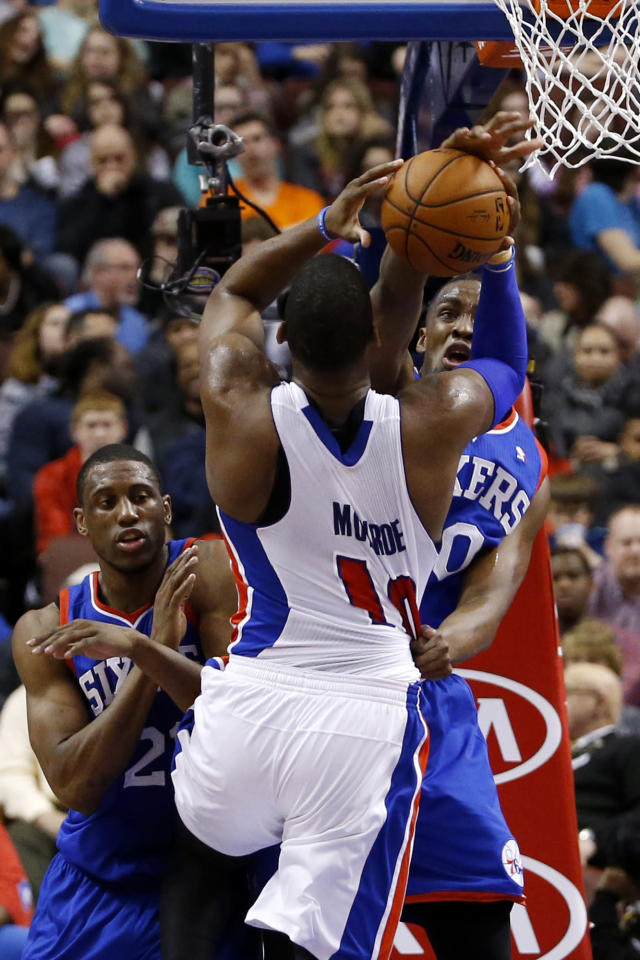 Detroit Pistons' Greg Monroe, center, tries to shoot past Philadelphia 76ers' Jarvis Varnado, right, and Thaddeus Young during the first half of an NBA basketball game on Saturday, March 29, 2014, in Philadelphia. (AP Photo/Matt Slocum)