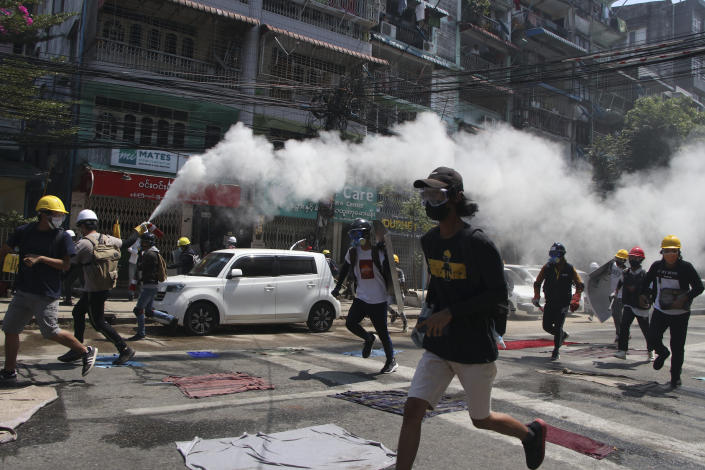 An anti-coup protester discharges a fire extinguisher to counter the impact of the tear gas fired by police during a demonstration in Yangon, Myanmar, Monday, March 8, 2021. Large protests have occurred daily across many cities and towns in Myanmar. (AP Photo)